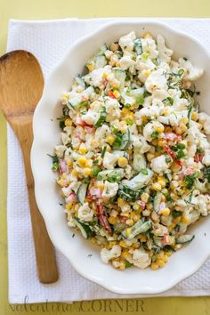 Cauliflower Corn and Cucumber Salad with a wooden spoon.