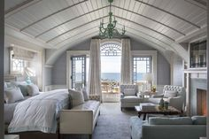 In the master bedroom, a boat-like bow ceiling sits within a dutch gambrel roof. The antique mirror above the fireplace conceals a TV; beyond the expansive Palladian window, a small balcony faces the ocean.
