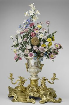 """Vincennes porcelain factory (1738-56): """"The Sunflower clock"""" (c. 1752), a gilt bronze clock in the form of a sunflower, mounted into the centre of a Vincennes porcelain urn shape vase containing a bouquet of flowers, also of Vincennes porcelain, on stems of green laquered brass wire"""