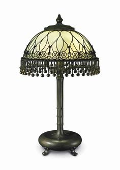 TIFFANY STUDIOS A FILIGREE TABLE LAMP, CIRCA 1910 glass, patinated bronze 28 in. (71 cm.) high, 16 in. (40.5 cm.) diameter of shade base stamped TIFFANY STUDIOS NEW YORK 88435