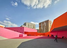 Hot pink and orange paintwork accentuate niches in the wooden facade of this school designed by French office Dominique Coulon & Associés for the Parisian suburb of Colombes