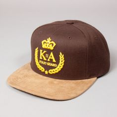 King branded snapback cap. Made on the same production line as our Starter branded hats and carries the exact same low profile block, shape and construction. Made in the classic pinch panel construction, with the front panel middle seam running just halfway down the front. Brown crown with light brown suede peak, yellow 3D stitched logo and matching yellow snap adjuster, with blue King woven label and customised interior Reign Supreme hat taping