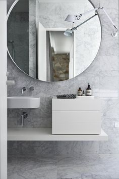 Carrara marble is a classic bathroom staple, but the oversized mirror and squared-off accessories make for a transitional space