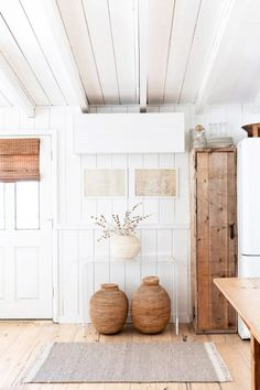 whitewashed cottage with shiplap walls and natural wood furnishings. / sfgirlbybay