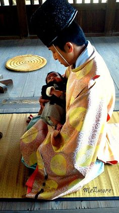 Shinto Priest with a Child- previously the infant mortality rate in Japan was high so infants are always blessed by a Shinto priest.