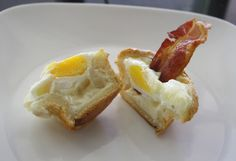 Breakfast in a Muffin  1 package refrigerated biscuits (the kind in the tube)  large eggs (one for each biscuit)  monterey jack or cheddar cheese  butter to grease the muffin tin  salt and pepper  bacon