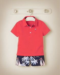 Bright coral and sailboat print swim trunks.