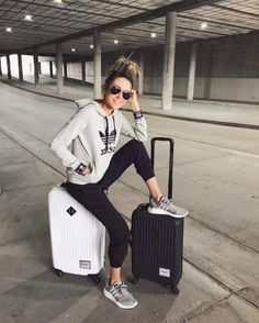Christine Andrew is seen in a simple but stylish grey Adidas hoodie, with black joggers and matching grey sneakers, This sporty chic style is perfect for travelling long journeys. Sweater: Adidas.