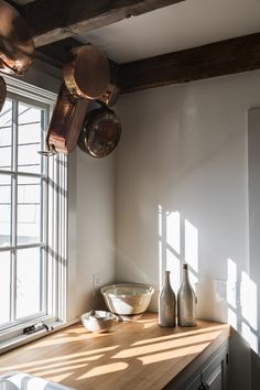In another corner of the kitchen, copper pans hang from iron wall hooks affixed to the timber rafters.