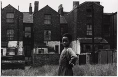Bleak: A young girl stands in front of a row of terraced houses in Manchester's Moss Side. During the 1960s and early 1970s, Manchester City Council demolished many of the Victorian and Edwardian terraced houses to the west of Moss Side and replaced these with new residential properties