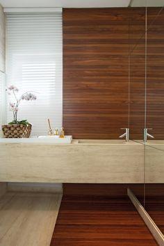 O lavabo tem piso e bancada em mármore Travertino (Marmoraria Gran-Norte) com cuba esculpida e painel em madeira natural (Incomap Móveis)