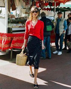 Jeanne Damas com blusa vermelha de manga longa, saia mídi estampada, rouje, espadrille, bolsa de palha, óculos de sol, batom vermelho, estilo das francesas, musas de estilo francesas