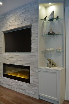 One end of fireplace wall with custom cabinetry, Erthcoverings Silver Fox stone, and Dimplex BLF50 electric fireplace. Design by Stylish Fireplaces.