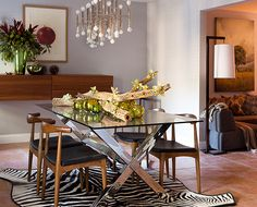 Chrome and glass table from West Elm. Chandelier and sconces by Jonathan Adler. Teak and black leather chairs from Cantoni. Wall-mounted buffet from BoConcept.