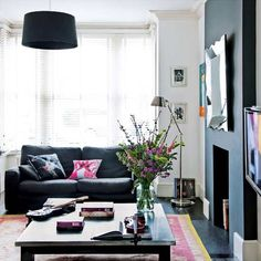 Love the dark chimney breast and pink accent cushions