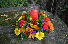 Autumn Light - Gillespie Florists, Indianapolis IN The Autumn Light bouquet is created with red carnations, fall daisies, yellow solidago, purple statice, glycerin fall oak leaves, a small red pillar candle and a keepsake hurricane with decorative a copper wire wrap.