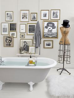 Turn your bathroom into a work of art by hanging black-and-white pictures in a variety of sizes. #decorating #artideas