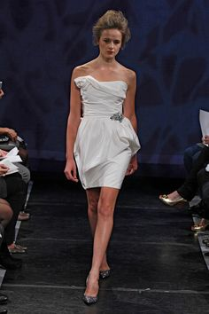 GIGI, RIVINI by Rita Vinieris - This little white dress has an asymmetrical, delicately gathered peplum, accented with a crystal beaded appliqué. The asymmetrical draped bodice finishes into a neckline rosette. Bridal Gown Styles, Wedding Dress Styles, Designer Wedding Dresses, Mini Wedding Dresses, Bridal Dresses, Wedding Gowns, Reception Dresses, Mon Cheri Bridal, Rehearsal Dress