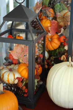 Fall DIY decorating idea - use an outdoor candle lantern with mini pumpkins, gourds, and fall leaves #falldecorating