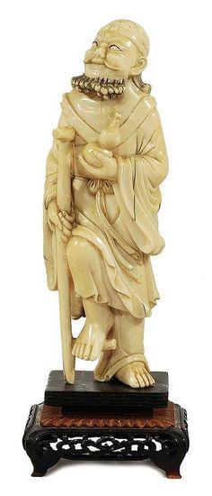 STATUETTE DE PELERIN EN IVOIRE, Chine 19-20ème En position debout sur un pied, reposant sur son bâton, le genou plié. Il tient dans la main une double-gourde, souriant dans un état de contentement. Dimensions : 17,5 x 6,5 cm (sans le socle)