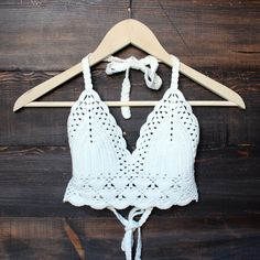 This crochet crop top radiates bohemian vibe! Beautiful halter crochet crop top featuring triangle detailing, scalloped open crochet trim at front hem and fully adjustable ties at back and neck. Can d