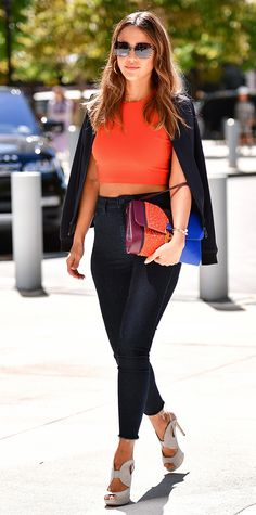 Jessica Alba in an orange crop top and high-waisted dark wash skinny jeans. Alba added a pair of slate gray Nicholas Kirkwood peep-toe Eclipse platform sandals. She draped a sweater over her shoulders, and accessorized with a pair of large sunglasses, and a tri-colour clutch in oxblood, mandarin, and royal blue while attending NYFW in New York City.