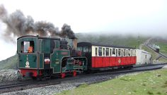Snowdon Mountain Raiway trains pass at Clogwyn. No.6 'Padern' is ascendind while No.2 'Enid' is descending out of the clouds.     ..photo by A. M. Hurrel - July 2005           ..commons-wikimedia.org