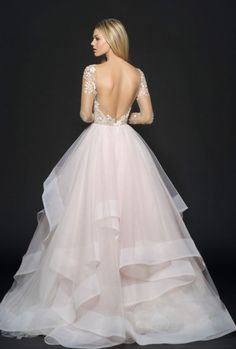Stunning low v-shaped back design long-sleeve wedding dress with cascading tulle skirt; Featured Dress: Hayley Paige