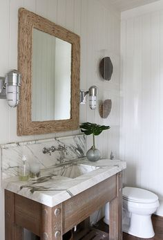 Andrew Howard interior Design      Amazing bathroom with white beadboard walls framing rectangular driftwood mirror flanked by marine sconces over marble top sink and vanity with polished nickel wall-mounted faucet set. Bathroom features stacked tortoise shells in shadow boxes over toilet and hardwood floors.