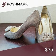 Stunning silver heels! Worn once to a wedding event, they are silver heels with a little bit of bronze mixed in for the perfect look to any nice event! Love the rose detail over the toes! Caparros Shoes Heels