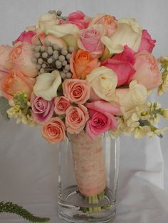 Hand-Tied Bridal Bouquet featuring Peach Juliett David Austin Roses, Rosita Vendela and Ivory Vendela Roses, Pink Blush Roses, Peach Verselia Roses, Silver Brunia, Ivory Stock stems and Gray Dusty Miller Foliage.  The handle is wrapped in double sided peach satin ribbon and topped with a delicate ivory lace ribbon.