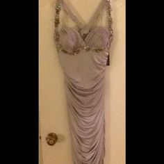 Faviana Couture Cocktail Dress Size L NEW w/Tags Faviana Couture formal prom cocktail dress Size L * 100% Polyester * Cut out back * Color-Loght Grey/Silver * Built in. Use support * Intricate beading * Stretch material * Mid calf length * Style 6200. This garment is from a major film studio wardrobe department. Faviana Couture Dresses Prom