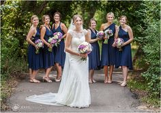 Bride poses with her bridesmaids along the treelined path at Chatfield Botanic Gardens in Colorado. - April O'Hare Photography http://www.apriloharephotography.com #ChatfieldBotanicGardens #DenverBotanicGardensChatfield  #ColoradoWedding #DenverWedding #ColoradoRusticWedding #ColoradoGardenWedding
