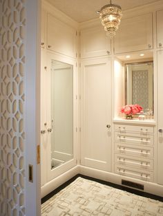 Little touches of elegance, a dainty chandelier and glass knobs, set the tone for this luxurious space.