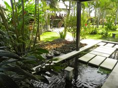 Balinese home fish pond design with fountain in large garden