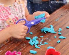 Cutting Play Dough with Plastic Scissors for fine motor practice in preschool.