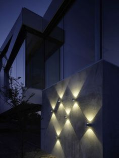 We love this clever use of multiple outdoor wall lights to create a textured feature of layered light.