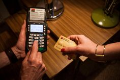 A customer paying by debit card at a Paris furniture store. Americans will soon have access to debit and credit cards with security chips, w...