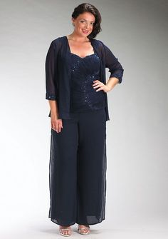 See plus size mother of the bride pant suits.  This dark navy blue formal dress has a sheer long sleeve jacket.  The bust line is cut with a sweetheart design.  The pants for this mother of the bride attire are made in chiffon.  Get more inspiration for plus size mother of the bride dresses (and pant suits) at www.dariuscordell.com
