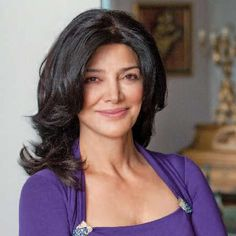 Shohreh Aghdashloo w/ shoulderlength wavy raven hair smiling in indigo chemisier w/ neckline clasps