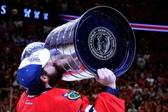 Corey Crawford #50 of the Chicago Blackhawks celebrates by kissing the Stanley Cup.