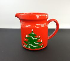 "A ceramic serving pitcher by Waechtersbach Germany... green Christmas Tree pattern on red body... size 28 ounce... 5.5"" tall... weight 1.5 lbs Very Good condition estate item... looks unused... no chi"