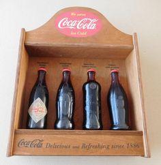 """Advertising Display Coca-Cola with 4 different bottles 20th century  Heel Mooie Nostalgische Houten Reclame Display Coca-Cola met daarin een set van 4 Coca-Cola flessen in de Originele doosNo.1 - Hutchinson Bottle - 1899No.2 - Straight wall Bottle - 1900No.3 - Samuelson Contour Bottle - 1915No.4 - Historic Contour Bottle - 1916Op de houten Display staat de tekst """" Coca - Cola Delicious and Refreshjing sing 1886""""Afmetingen:Kastje - ca. 44.5 x 35 x 9 cm.Flesjes - ca. 19 cm. (hoogte) / 6 cm…"""