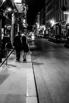 Paris Street at Night. by johnnygphoto A couple walks down the street after an evening out in Paris