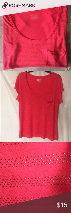 CK embellished t-shirt I have a coral pink CK t-shirt NWOT. The size is L, has a small pocket and has studs in a striped pattern, feels very soft! Make me an offer! Calvin Klein Tops Tees - Short Sleeve