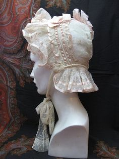Victorian lace bonnet with ruffles and petal-pink silk ribbons and long, lacy chin-ties.