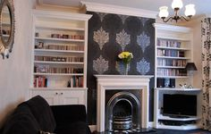 Silver fireplace; statement wallpaper ; thick dark carpet