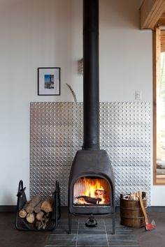 A metal panel protects the wall behind a wood-burning stove and adds a visual focal point within a Canadian vacation home. Photo by: Lorne Bridgman