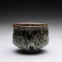 Stoneware tea bowl with layered tenmoku and white glazes.