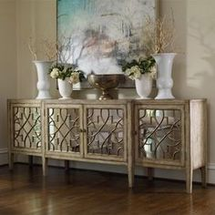 """Four-door mirrored console table with a fretwork motif.   Product: Console table   Construction Material: Hardwood solids, oak veneers and mirrored glass     Color: Natural   Features:   Distressed finish   Adds distinction to any room   Beautiful mirror front    Dimensions: 38"""" H x 105"""" W x 20"""" D"""